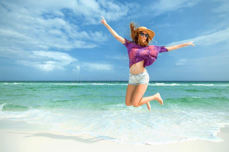 妇女为在白色沙子海滩的喜悦跳 免版税库存图片