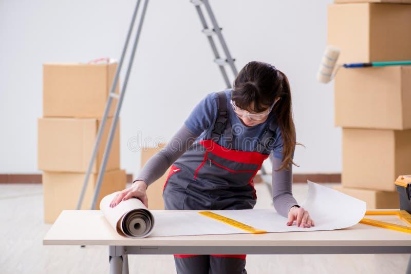 妇女为墙纸工作做准备 库存照片