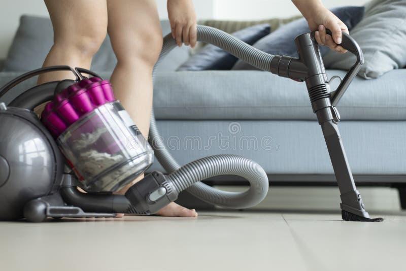 妇女为定期清洁使用vacumming的机器 免版税库存照片