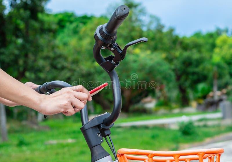 妇女为自行车租务使用流动应用 免版税库存照片