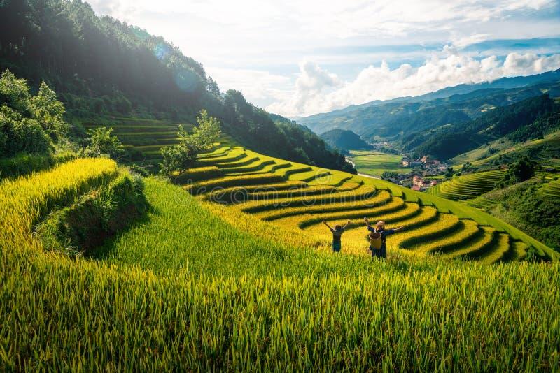 妇女举在米领域的农夫和女儿胳膊露台在日落在Mu Cang柴, YenBai,越南 库存照片