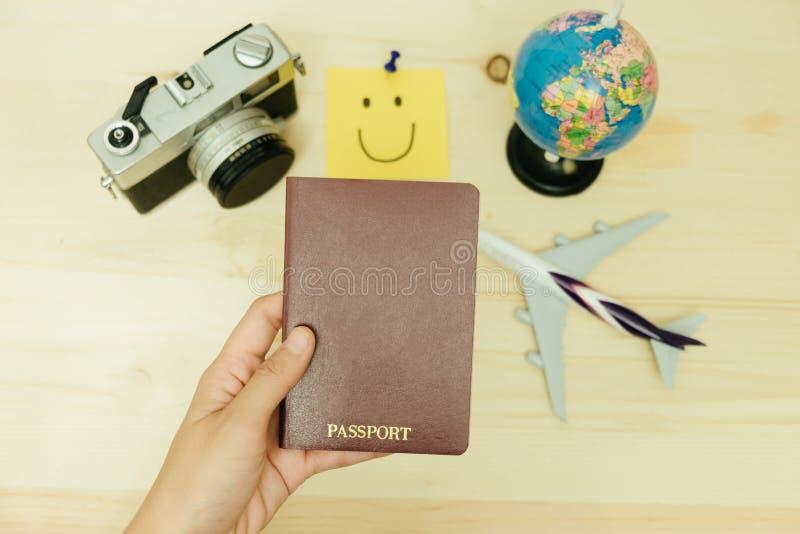 妇女举行护照的手有平面模型,减速火箭的照相机, worl 免版税库存照片