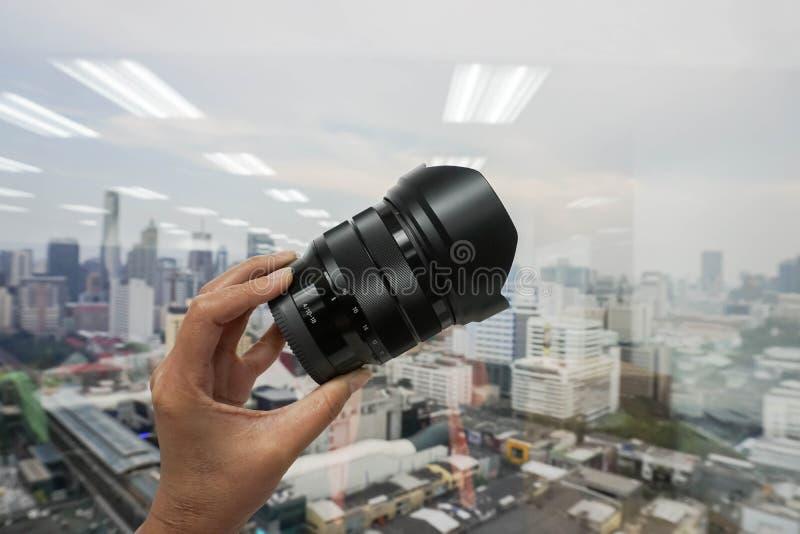 妇女举行摄象机镜头在手中 免版税库存照片