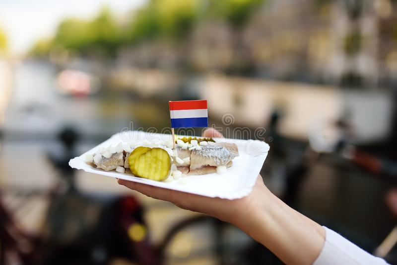 妇女举行板材著名鲱鱼钓鱼用葱和黄瓜在阿姆斯特丹上,荷兰快餐市场  免版税库存图片