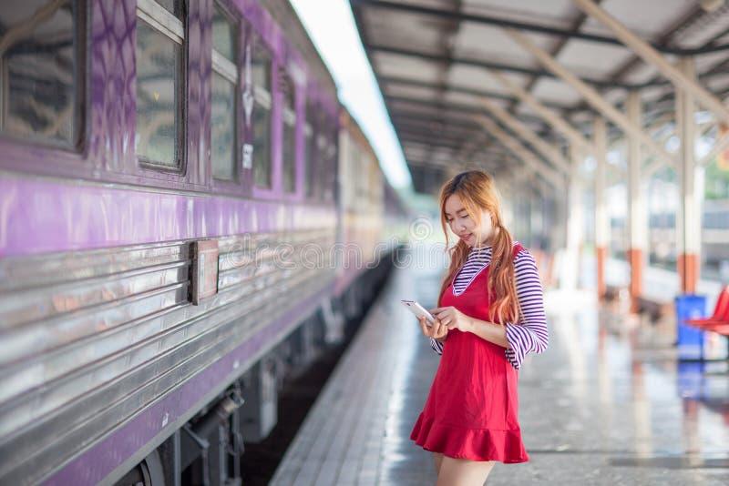 妇女乘在铁路st平台的火车搜寻地点旅途  免版税库存照片