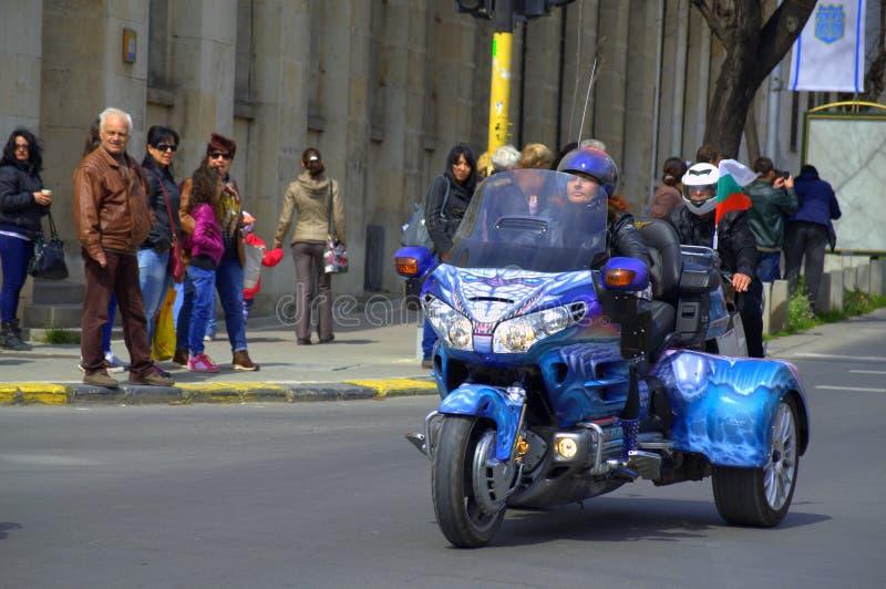 妇女乘驾五颜六色的摩托车 免版税库存照片