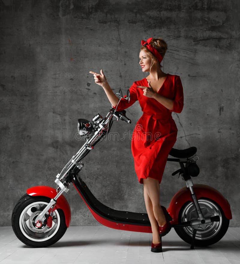 妇女乘驾坐指向手指的摩托车自行车滑行车画报减速火箭的样式笑微笑的红色礼服 免版税图库摄影
