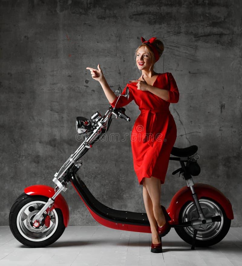 妇女乘驾坐指向手指笑的微笑的红色礼服的摩托车自行车滑行车画报减速火箭的样式 免版税库存照片