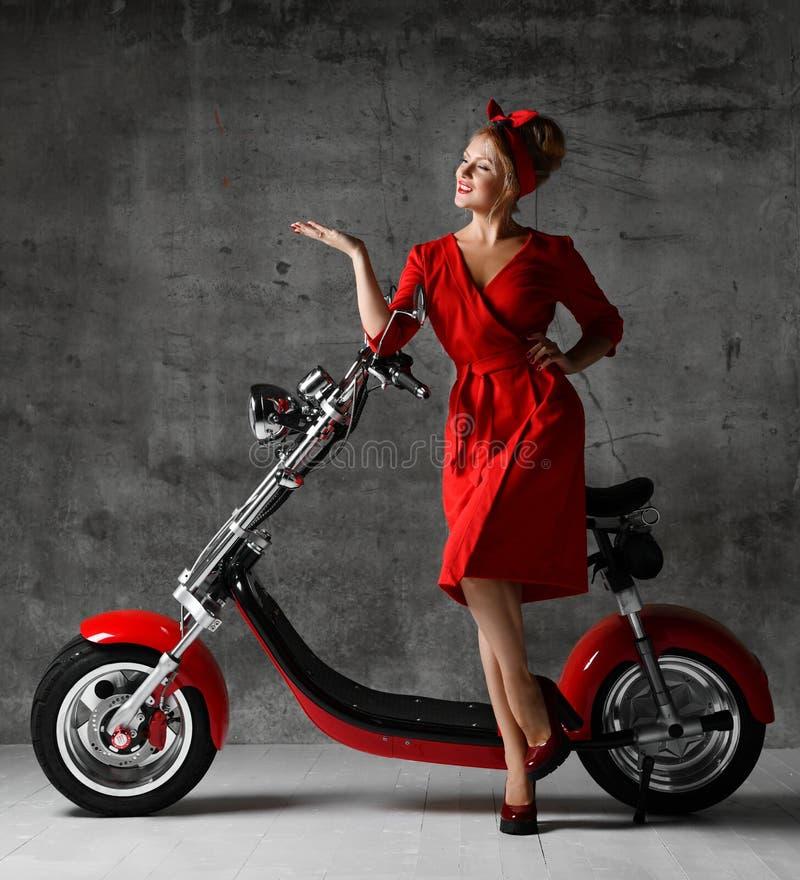 妇女乘驾坐指向手笑的微笑的红色礼服的摩托车自行车滑行车画报减速火箭的样式 免版税库存图片