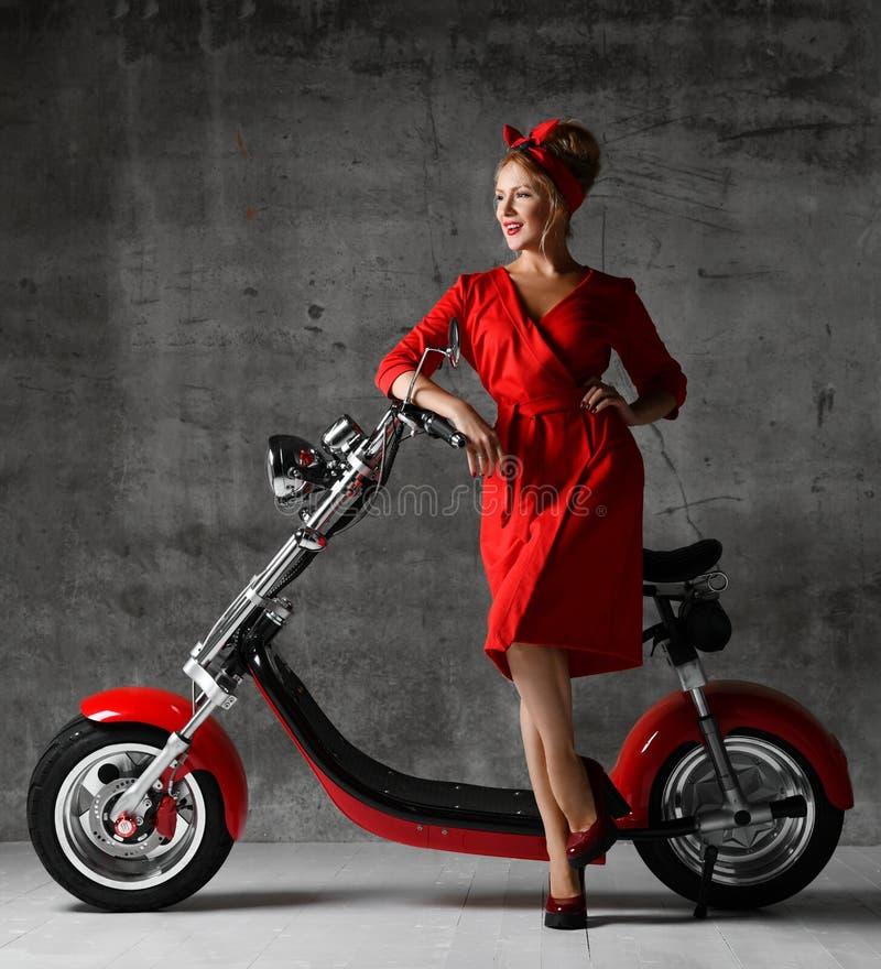 妇女乘驾坐摩托车自行车滑行车画报减速火箭的样式笑的微笑的红色礼服 免版税库存照片