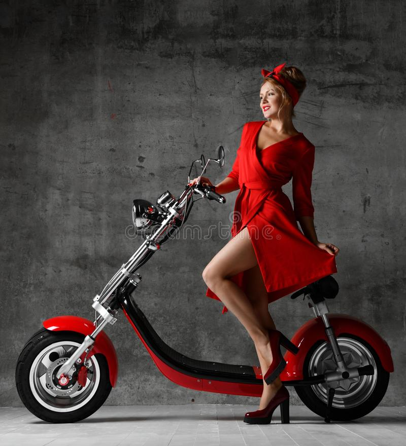 妇女乘驾坐摩托车自行车滑行车画报减速火箭的样式笑的微笑的红色礼服 库存图片