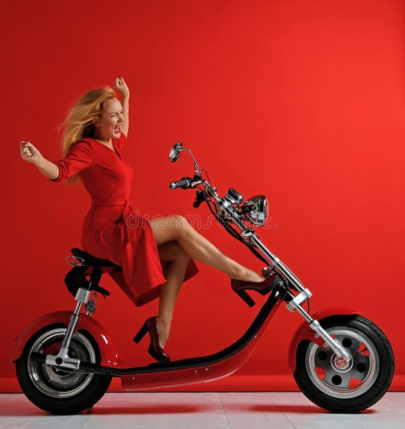 妇女乘驾新的电车摩托车自行车滑行车用手传播了自由标志笑的微笑在红色背景 免版税库存图片