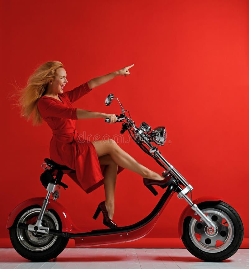 妇女乘驾新的电车摩托车自行车滑行车用指向自由标志笑的微笑的手手指 免版税库存照片