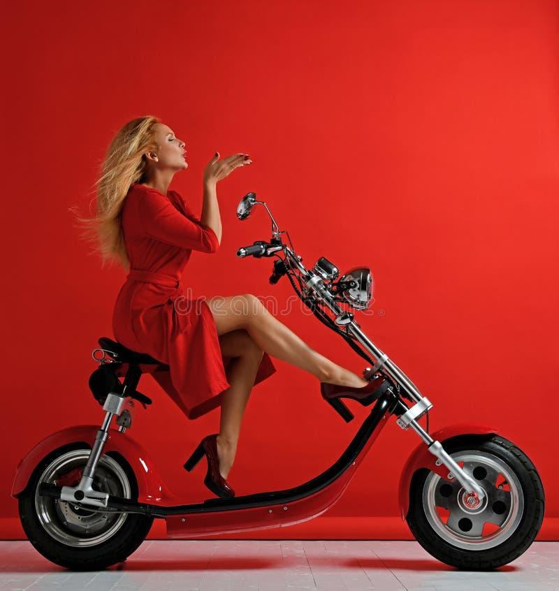 妇女乘驾新的电车摩托车自行车滑行车礼物在红色礼服打击亲吻标志的新年2019年与在红色的嘴唇 库存照片
