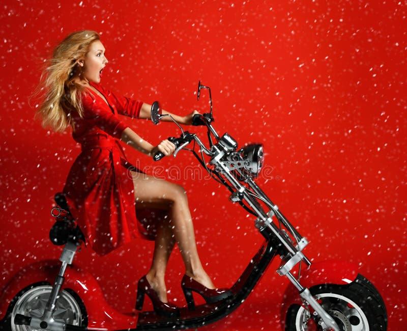 妇女乘驾新的电车摩托车自行车滑行车礼物在红色礼服的新年2019年在惊奇的红色背景 库存图片
