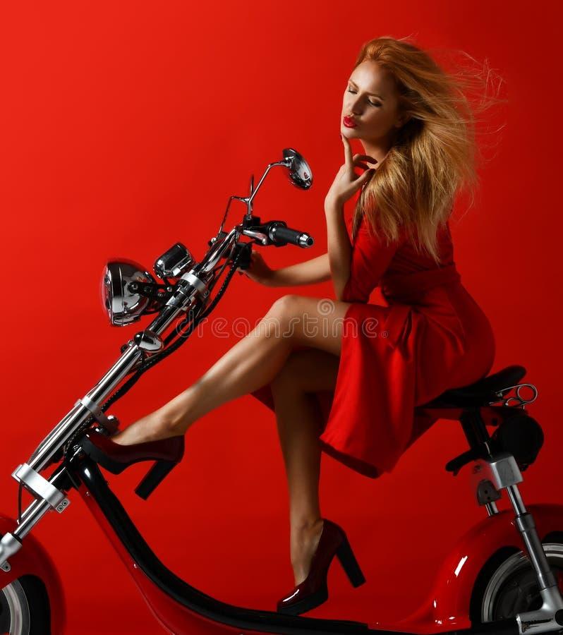 妇女乘驾新的电车摩托车自行车滑行车礼物在红色礼服的新年2019年在红色背景 免版税图库摄影