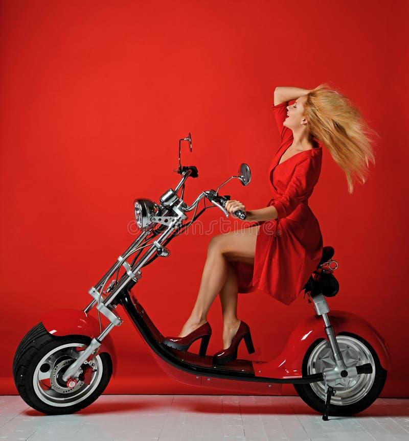 妇女乘驾电摩托车自行车滑行车在红色礼服愉快笑的微笑的新年2019年在红色 图库摄影