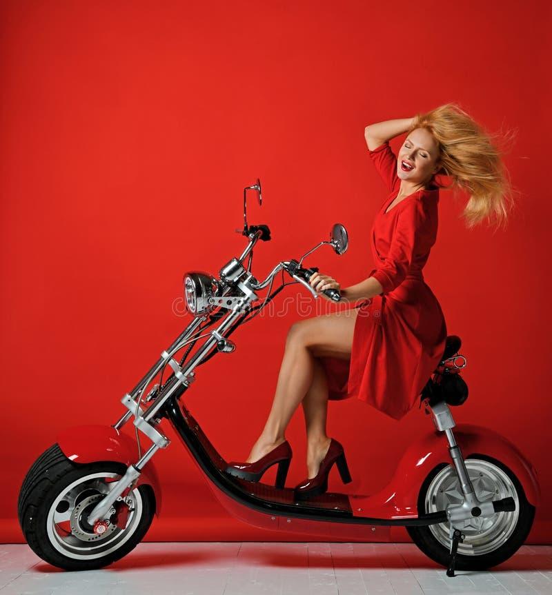 妇女乘驾电摩托车自行车滑行车在红色礼服愉快笑的微笑的新年2019年在红色 免版税库存照片