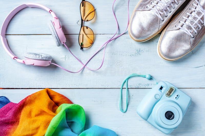 妇女书桌,时尚博客作者,秀丽技术辅助部件:立即照片照相机、五颜六色的手帕、桃红色耳机和 免版税库存图片