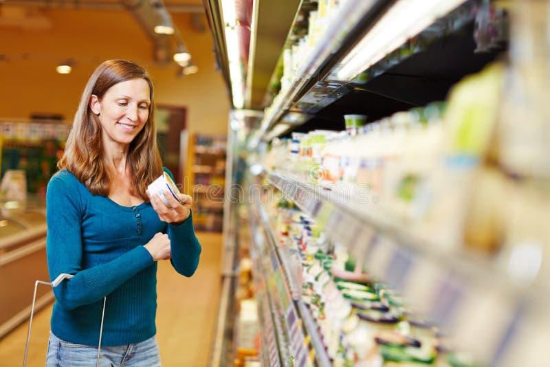 妇女买的乳制品在超级市场 库存照片