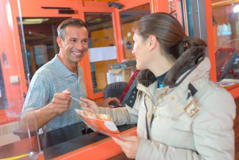 妇女买的票通过舱口盖 免版税库存照片