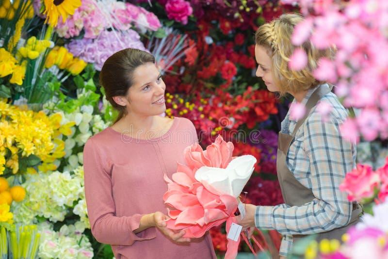 妇女买的花在园艺中心运载手提篮微笑 库存图片