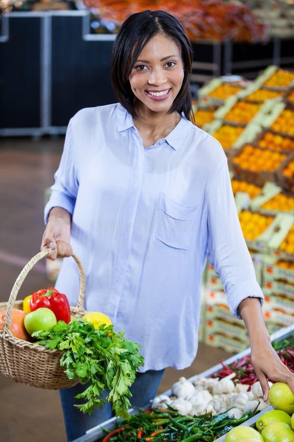 妇女买的蔬菜和水果在有机部分 图库摄影