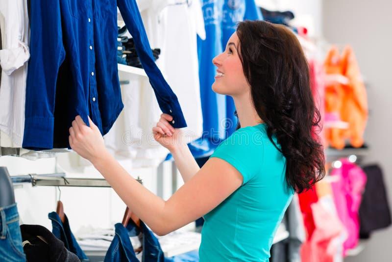 妇女买的衣裳在商店 免版税库存图片