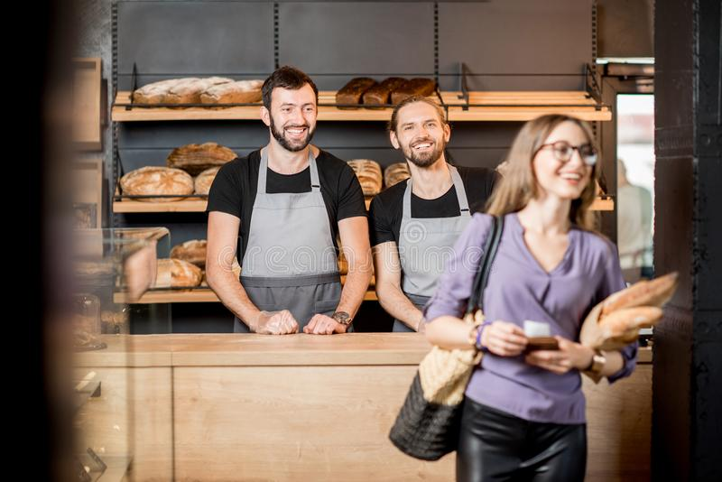 妇女买的面包在有人卖主的面包店商店 库存照片