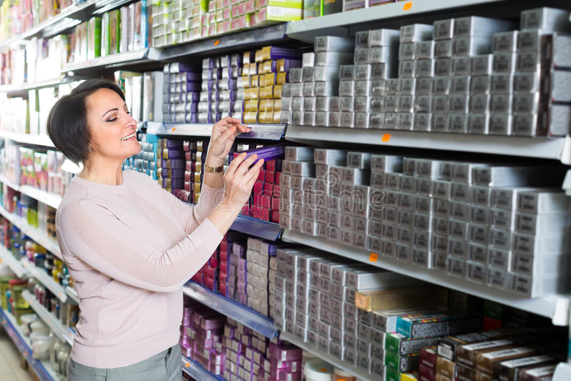 妇女买的头发染料在商店 库存照片