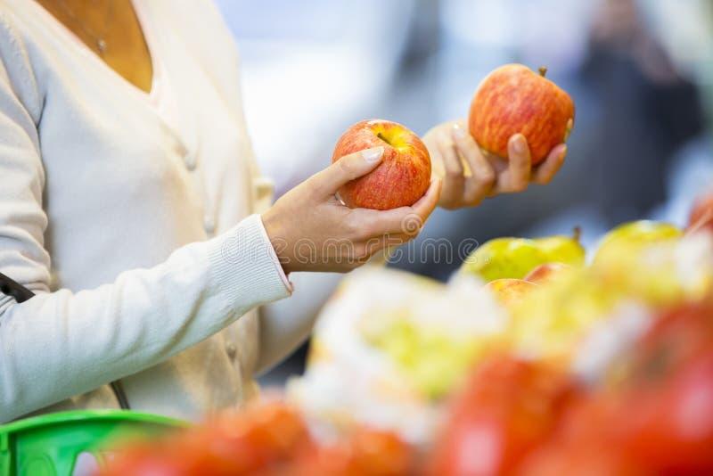 妇女买水果和蔬菜在市场上 图库摄影