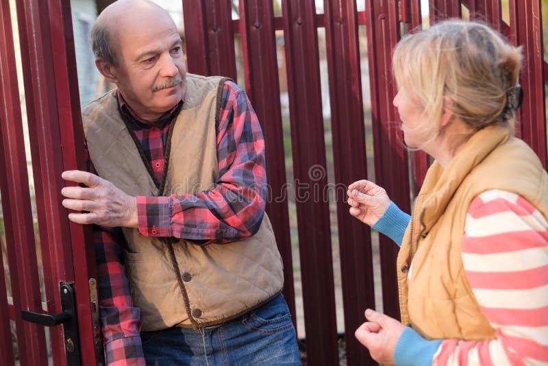 妇女争吵并且有与她的邻居的冲突在篱芭门 库存图片