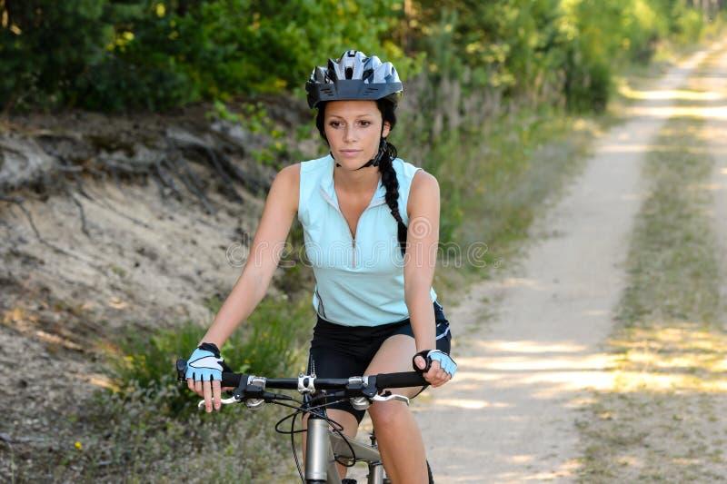 妇女享受消遣山骑自行车 免版税库存照片