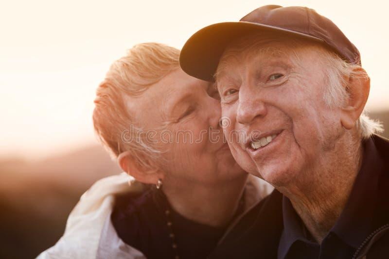 妇女亲吻微笑的人 免版税图库摄影