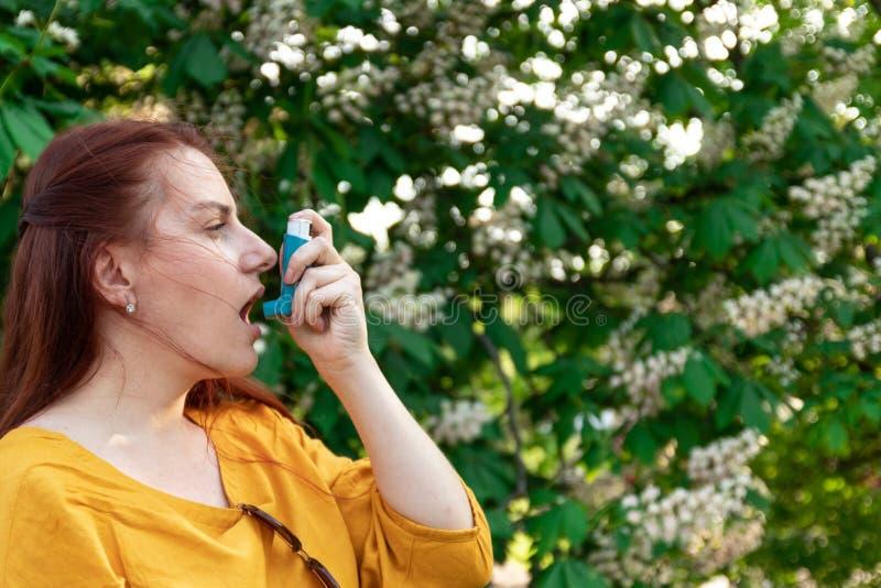 妇女从中哮喘病发作拯救自己 痉孪吸入器 免版税库存图片