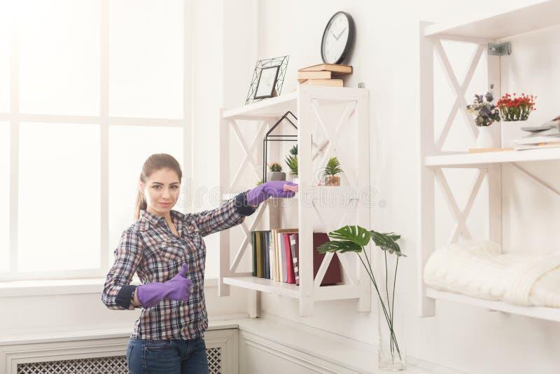 妇女从书架的清洁尘土 免版税图库摄影