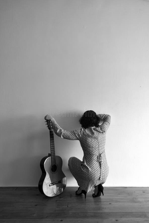 妇女从后面与在墙壁上的吉他 免版税库存照片