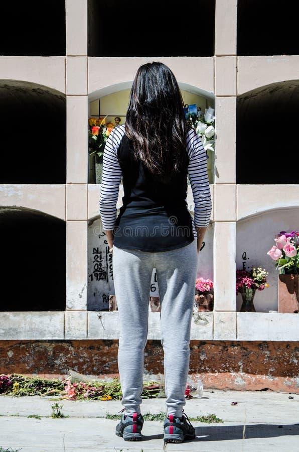 妇女从后面冥想坟墓亲人 图库摄影