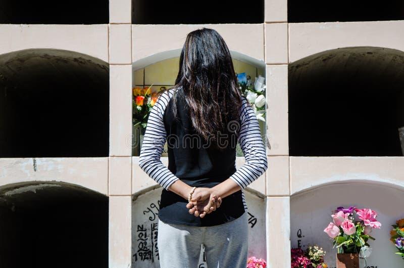 妇女从后面冥想坟墓亲人 库存照片