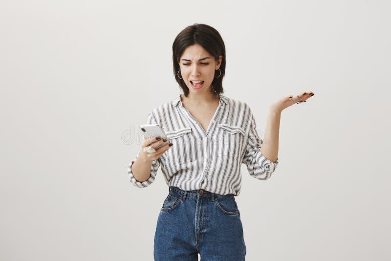 妇女从未知数收到了可笑消息 打手势与的懊恼和恼怒的逗人喜爱的深色头发的女实业家 免版税库存照片