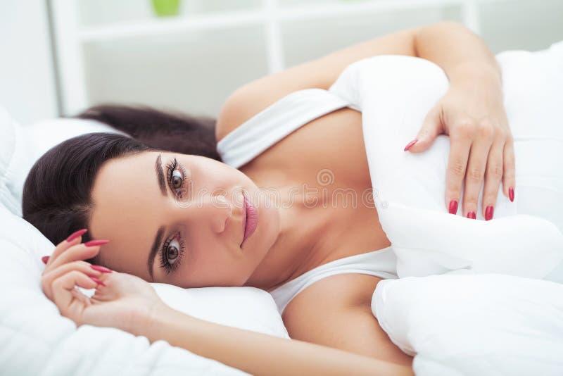 妇女从长的睡眠在打呵欠和舒展在t的床上唤醒 免版税库存图片