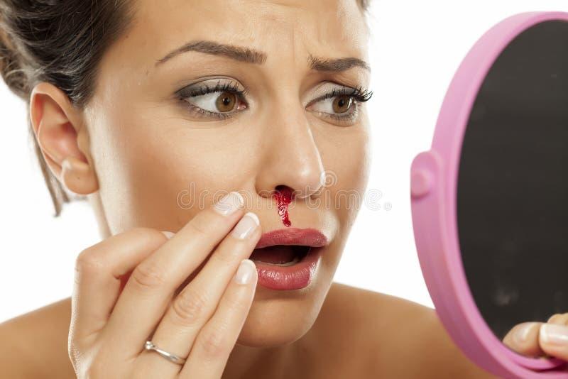 妇女以鼻血 免版税库存图片