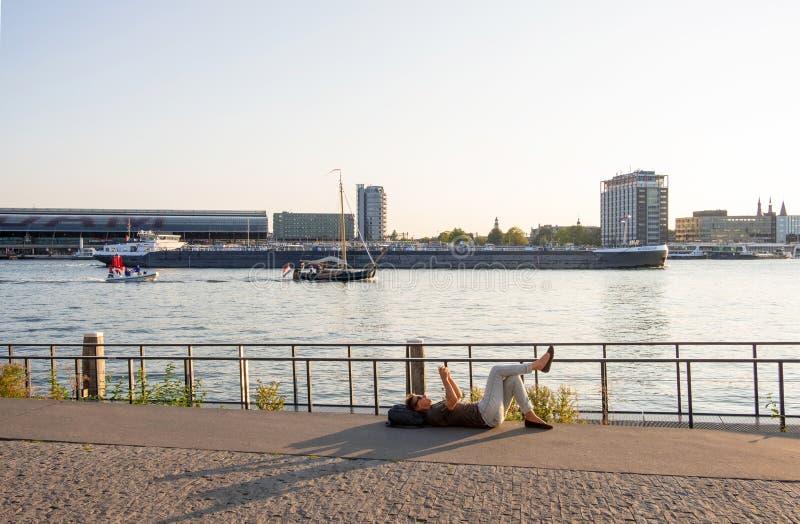 妇女休息的说谎在反对口岸和中央驻地的背景的阿姆斯特尔河河岸在阿姆斯特丹 免版税图库摄影