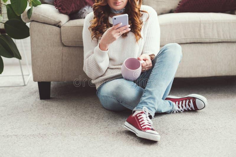 妇女休闲舒适家庭杯子浏览智能手机 免版税库存图片