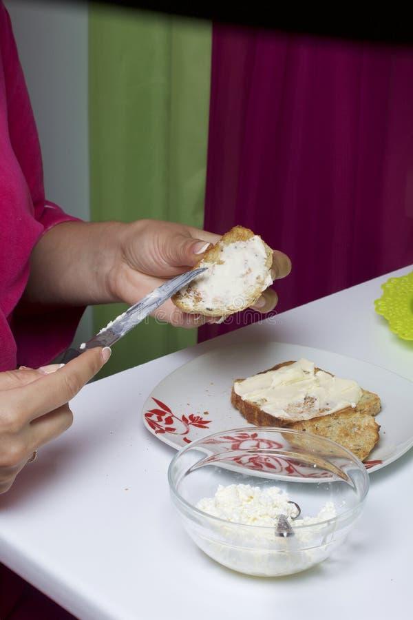 妇女传播黄油和酸奶干酪多士她自己的早餐 免版税图库摄影