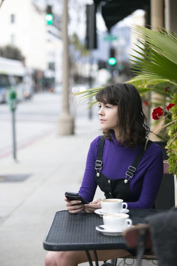 妇女传讯社会媒介的一个朋友,当等待在咖啡馆时 免版税库存照片