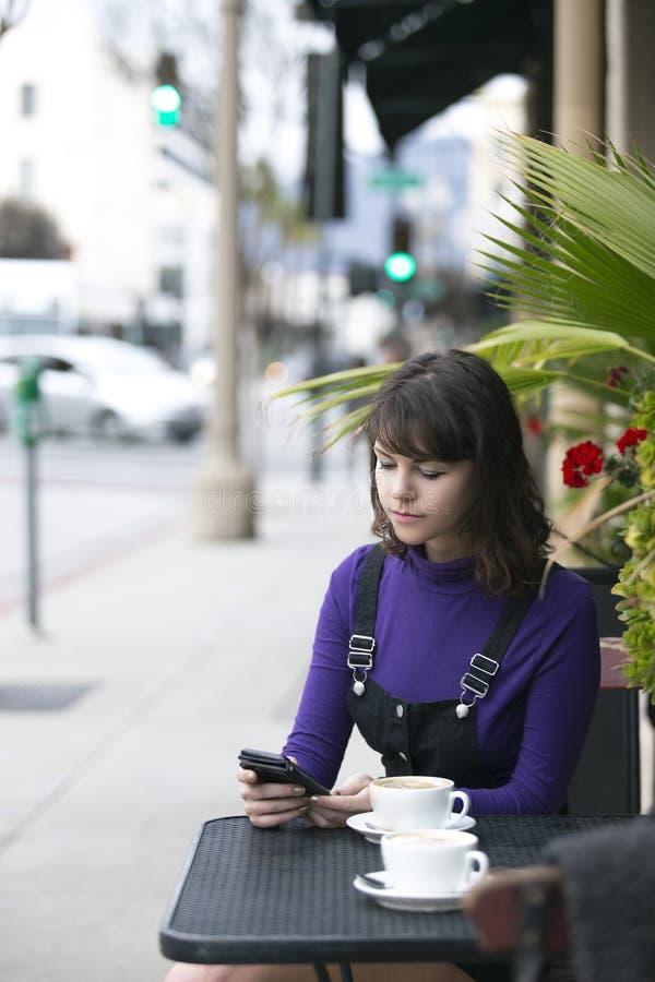 妇女传讯社会媒介的一个朋友,当等待在咖啡馆时 图库摄影