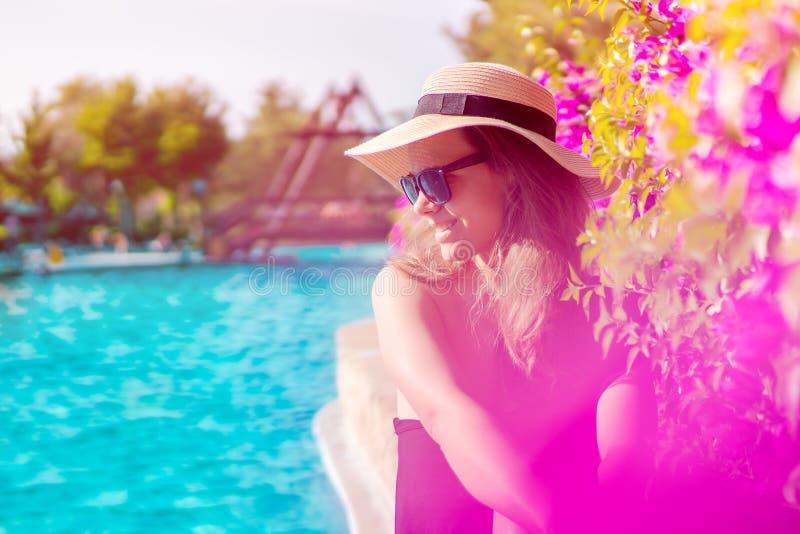 妇女佩带的太阳镜画象由水池的,得到棕褐色由游泳场 免版税库存照片