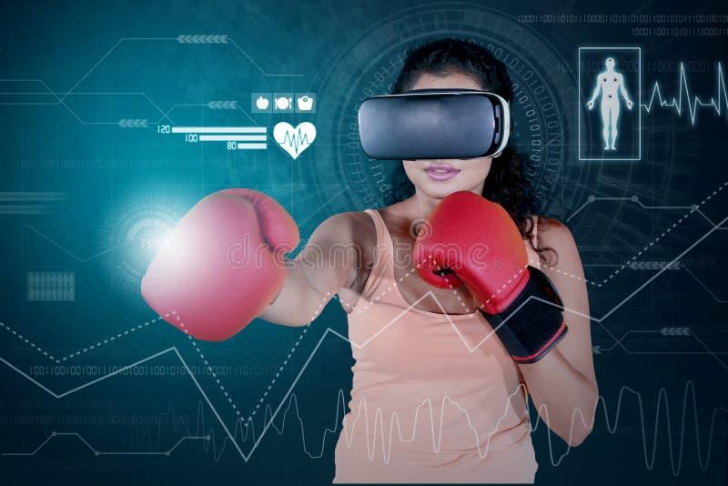 妇女佩带的拳击手套和VR玻璃 库存图片