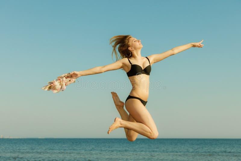 妇女佩带的比基尼泳装使用,跳跃在海附近 免版税库存图片